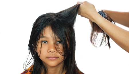 blow drier: A young Malay  Asian girl getting her hair dried by mother