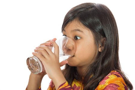 Young Malay  Asian girl drinking a glass of water photo