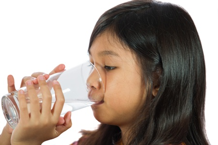 girl drinking water: Young Malay  Asian girl drinking a glass of water