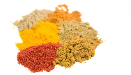 Various powdered spices over white background