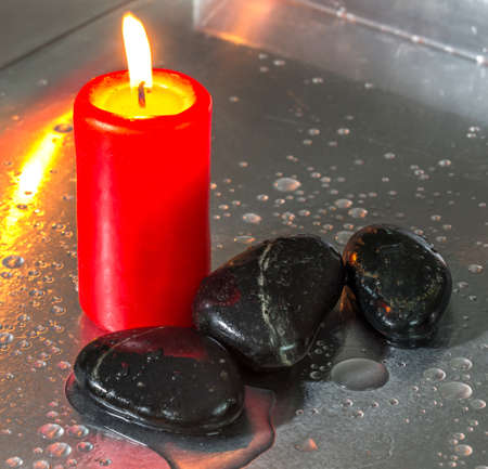 Zen stone with red candle and water droplets photo