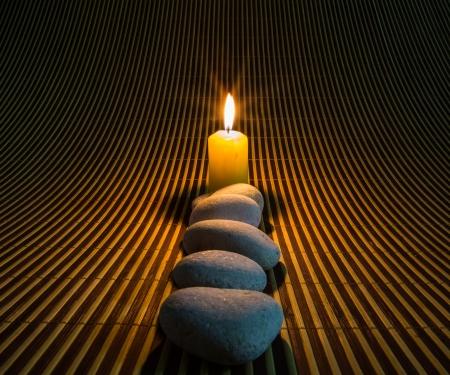 Zen stenen en gele kaarsen op een bamboe mat Stockfoto
