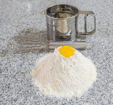sifter: Flour, egg yolk, egg beater and flour sifter on a granite counter surface