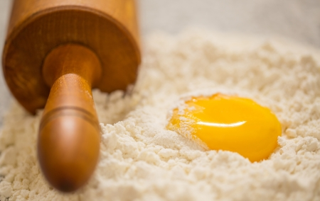 Pastry making preparation with egg, yolk, flour and rolling pin on a granite counter surface  photo