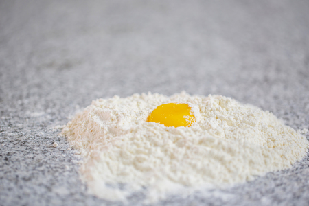 Flour and egg yolk  on a granite counter surface  photo