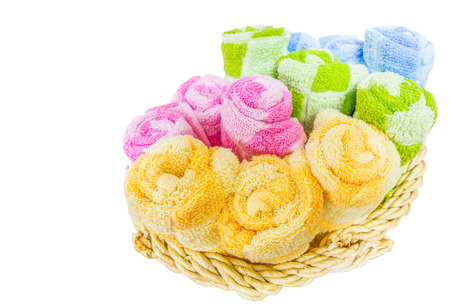 Rolls of different colors of towels in a wicker basket  photo