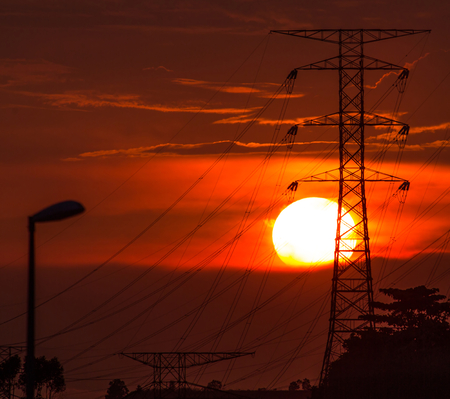 Sunset over the horizon with electric pylons photo