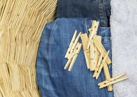 clothes peg: A bunch of clothes peg and laundry in a wicker basket