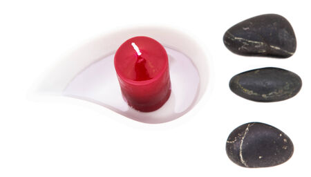 Aromatic red candle in a ceramic container and zen stones  over white background photo