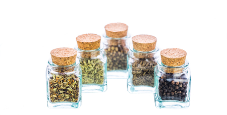 corked: Cilantro, cumin, black peppers and coriander seeds herbs and spices in small corked bottles  Stock Photo