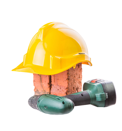 Safety helmet, red bricks and power drill over white background photo