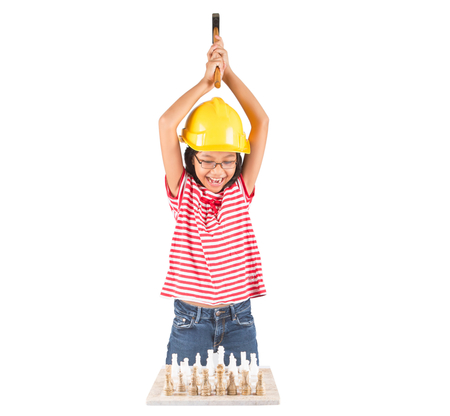 Concept image of little girl destroying a stone chess set with a hammer Stock Photo