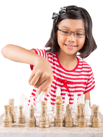 Little girl playing stone made chess over white background Stock Photo