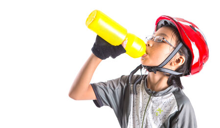 Little Asian Malay girl with cycling attire drinking water Stock Photo - 24403333