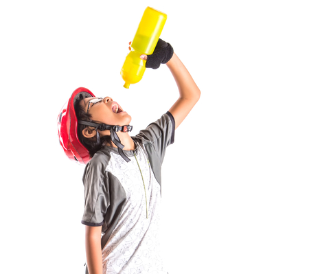Little Asian Malay girl with cycling attire drinking water  photo