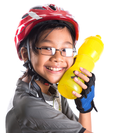 safe drinking water: Little Asian Malay girl with cycling attire and water bottle
