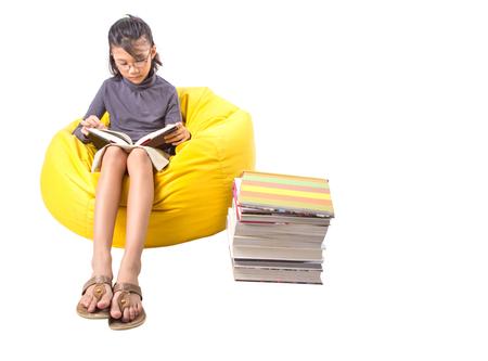 Joven chica asiática malayo leyendo un libro en una bolsa de frijol amarillo Foto de archivo - 24496152