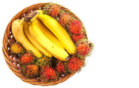 interleaved: Banana and rambutan in a wicker basket