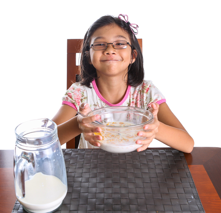 Young female asian child having breakfast of cereal milk and pieces of banana photo