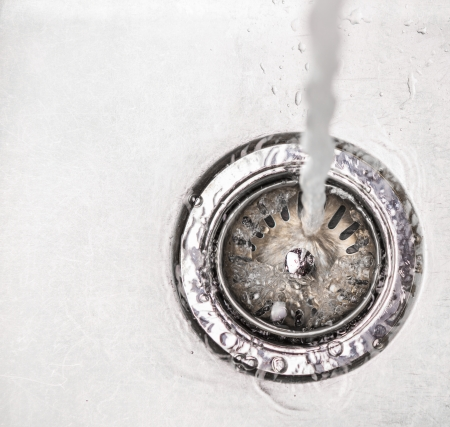 Wasser das Loch in einer Küchenspüle fließt nach unten Standard-Bild - 24826465