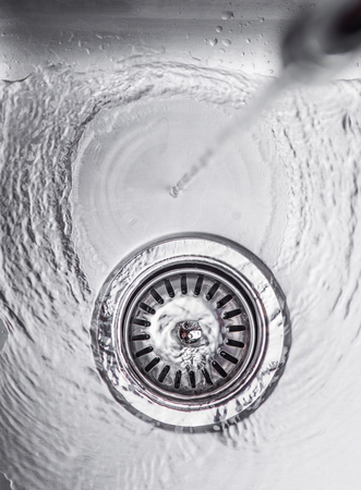 Water flowing down the hole in a kitchen sink photo