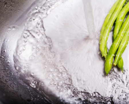 Washing green bean vegetables at the kitchen sink Stock Photo - 24826539