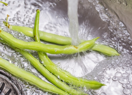 Washing green bean vegetables at the kitchen sink Stock Photo - 24826544