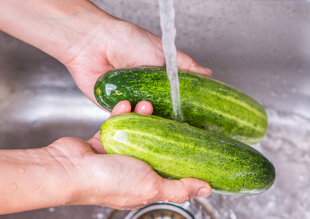 Female hands washing cucumber at the kitchen sink  photo