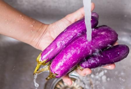 Female hands washing eggplant vegetables at the kitchen sink Standard-Bild