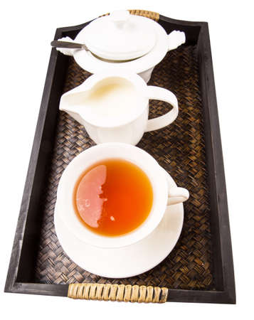 A cup of tea with sugar and milk in a wooden tray photo