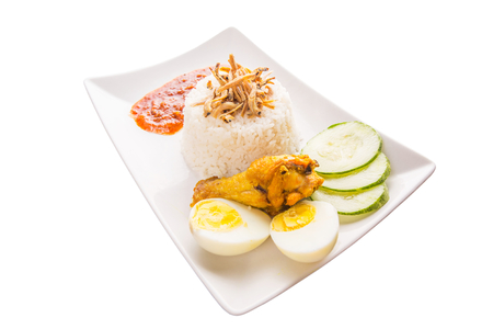 Nasi lemak a traditional and popular Malaysian spicy rice dish  Served with anchovy, chili sauce, cucumber, fried chicken and hard boiled egg   photo