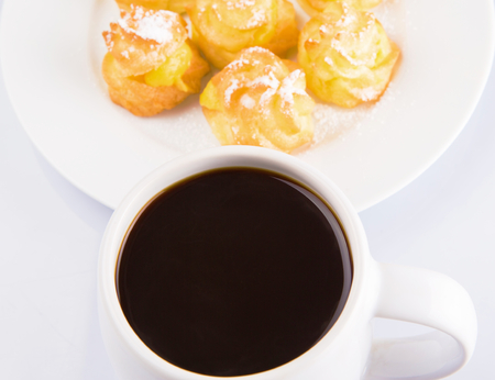 creampuff: Homemade cream puff and a mug of coffee Stock Photo