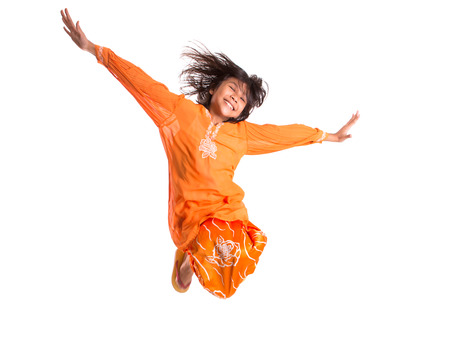 Young asian malay girl jumping happily wearing a traditional Malay dress the baju kurung