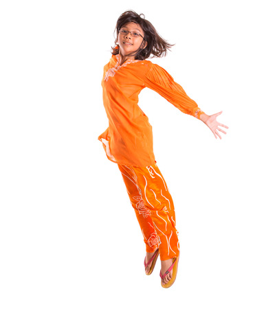 Young asian malay girl jumping happily wearing a traditional Malay dress the baju kurung  photo