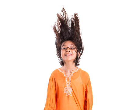Young Asian Malay girl having fun with her hair wearing a traditional Malay dress the baju kurung  photo