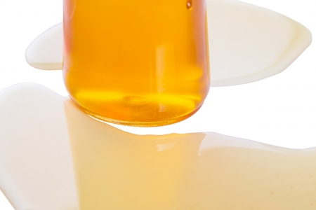 curative: A bottle of natural honey over white background Stock Photo