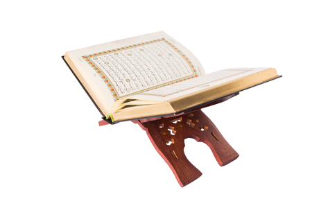 book of revelation: The Islamic scripture, the Holy Quran on a traditional wooden book stand over white background