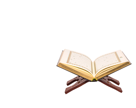 scripture: The Islamic scripture, the Holy Quran on a traditional wooden book stand over white background