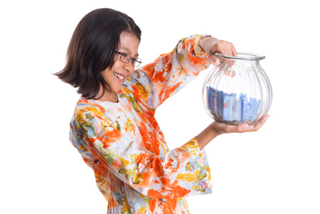 Young asian girl with money jar over white background photo