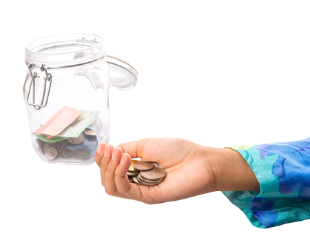 A little girl hands putting coin in a money jar  photo