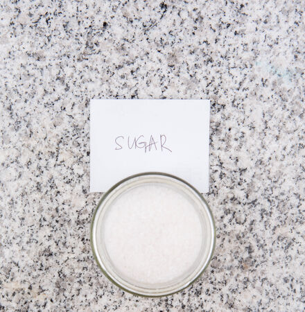 Salt and sugar in a glass bottle on granite surface  photo