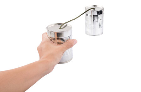 Female hand holding tin can telephone over white background photo