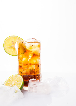 Cola drinks with ice cubes and lime over white background photo