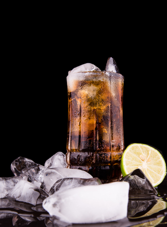 Cola drinks with ice cubes and lime over black background photo