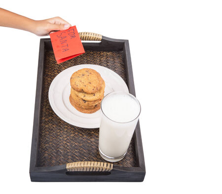 Young girl hands preparing milk, home made cookies and thank you note for Santa Claus photo