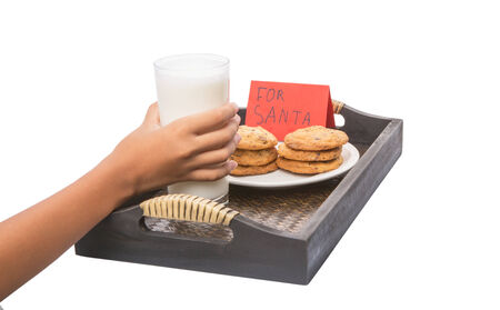 thank you note: Young girl hands preparing milk, home made cookies and thank you note for Santa Claus Stock Photo