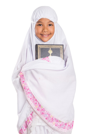 Young Asian Muslim girl reading Al Quran on a prayer mat over white background photo