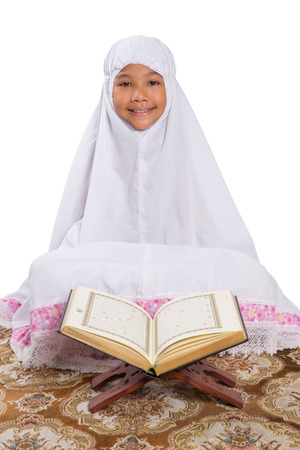 doa: Young Asian Muslim girl reading Al Quran on a prayer mat over white background Stock Photo