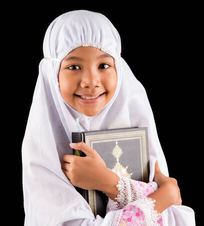 Young Asian Muslim girl in white hijab with Al Quran over black background Stock Photo - 27043416
