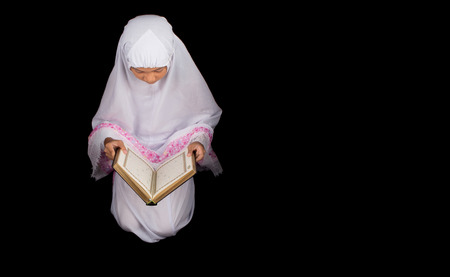 Young Asian Muslim girl in white hijab with Al Quran over black background photo